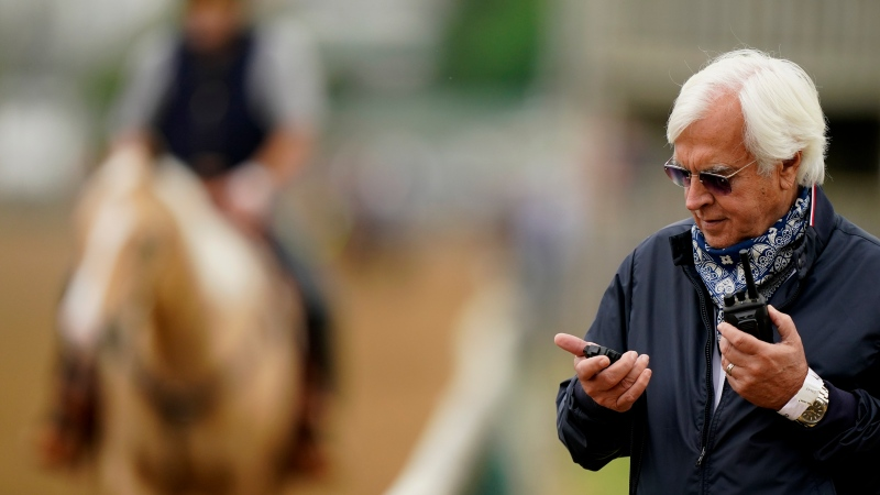 Trainer Bob Baffert checks his stopwatch while watching workouts at Churchill Downs Wednesday, April 28, 2021, in Louisville, Ky. (AP Photo/Charlie Riedel)
