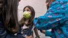 In this Wednesday, March 24, 2021 image from video provided by Duke Health, Alejandra Gerardo, 9, looks up to her mom, Dr. Susanna Naggie, as she gets the first of two Pfizer COVID-19 vaccinations during a clinical trial for children at Duke Health in Durham, N.C. (Shawn Rocco/Duke Health via AP)