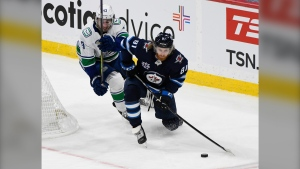 Winnipeg Jets' Kyle Connor (81) looks to pass the puck as Vancouver Canucks' Quinn Hughes (43) defends during second period NHL action in Winnipeg, Monday, May 10, 2021. THE CANADIAN PRESS/Fred Greenslade