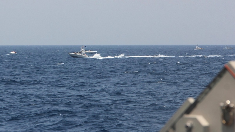 In this image provided by the U.S. Navy, an Iranian Islamic Revolutionary Guard Corps Navy (IRGCN) fast in-shore attack craft (FIAC) speeds near U.S. naval vessels transiting the Strait of Hormuz, on May 10, 2021. (U.S. Navy via AP)