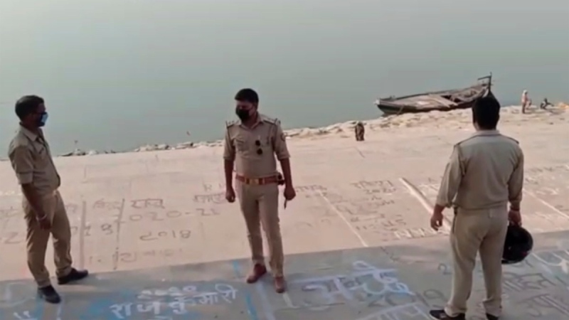 Police stand guard at the banks of the Ganges River where several bodies were found lying in Ghazipur district in Uttar Pradesh state India, on May 11, 2021. (KK PRODUCTIONS via AP)