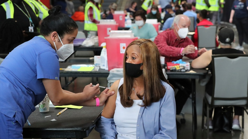 In this March 23, 2021, file photo, Anita Shetty, left, vaccinates Doris Lucas with a Pfizer vaccine in Atlanta. (Curtis Compton/Atlanta Journal-Constitution via AP, File)