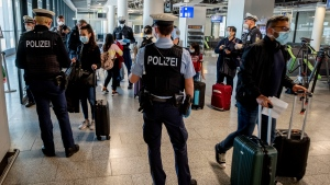 In this March 30, 2021, file photo, German federal police officers check passengers arriving from Palma de Mallorca for a negative Corona test as they arrive at the airport in Frankfurt, Germany. (AP Photo/Michael Probst, File)