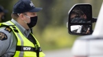 A motorist is reflected in a side-view mirror as he shows his identification to an RCMP officer at a COVID-19 travel checkpoint on the Trans-Canada Highway north of Boston Bar, B.C., on Friday, May 7, 2021. (Darryl Dyck / THE CANADIAN PRESS)
