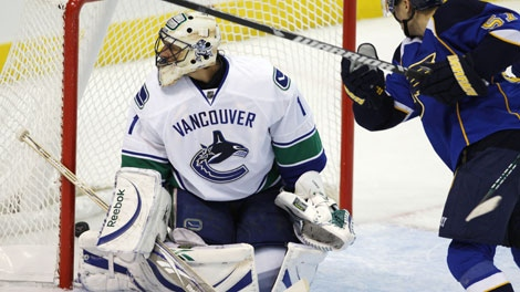 St. Louis Blues' David Perron scores a goal, his third of the game, against Vancouver Canucks goalie Roberto Luongo in the third period of an NHL hockey game Tuesday, Nov. 10, 2009, in St. Louis. The Blues beat the Canucks 6-1. (AP Photo/Tom Gannam)