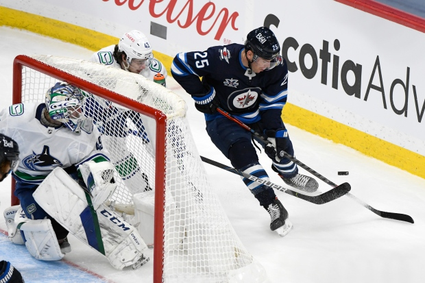 Winnipeg Jets' Paul Stastny (25) carries the puck around Vancouver Canucks' Quinn Hughes (43) during second period NHL action in Winnipeg on Tuesday May 11, 2021. THE CANADIAN PRESS/Fred Greenslade