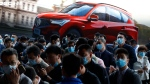 In this April 21, 2021, file photo, visitors attend the Shanghai Auto Show in Shanghai. (AP Photo/Ng Han Guan, File)