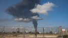 An Israeli soldier stands guard next to an Iron Dome air defence system as smoke rises from an oil tank on fire after it was hit by a rocket fired from Gaza Strip, near the town of Ashkelon, Israel, on May 12, 2021. (Ariel Schalit / AP)