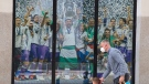 A man and a young boy walk past a Real Madrid poster of the team celebrating in a merchandising shop in Madrid, Spain, Monday, April 19, 2021. (AP Photo/Paul White)