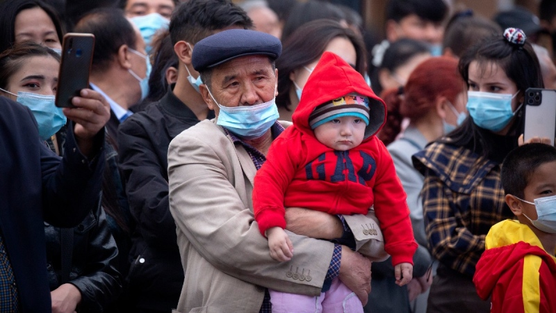 A man holds a child as they watch a dance performance at the International Grand Bazaar in Urumqi in western China's Xinjiang Uyghur Autonomous Region, Wednesday, April 21, 2021. (Mark Schiefelbein / AP)