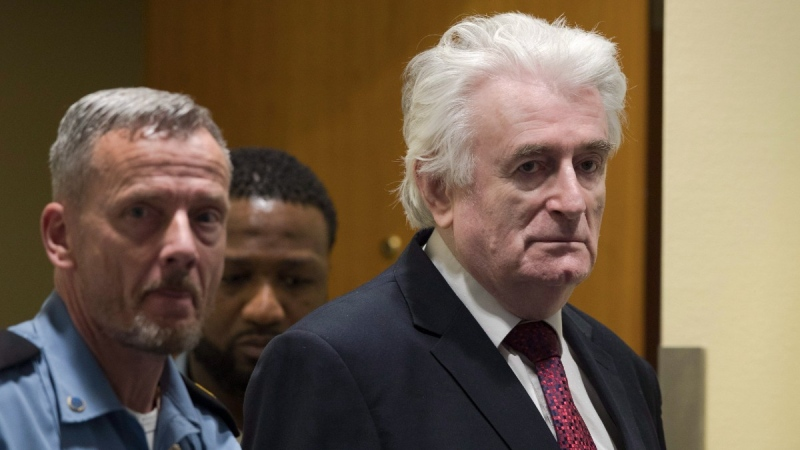 Former Bosnian Serb leader Radovan Karadzic enters the court room of the International Residual Mechanism for Criminal Tribunals in The Hague, Netherlands, on March 20, 2019.  (Peter Dejong / AP)