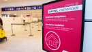 A sign reminds arriving passengers to quarantine against COVID-19 at Trudeau Airport in Montreal, Friday, Feb. 19, 2021. THE CANADIAN PRESS/Ryan Remiorz