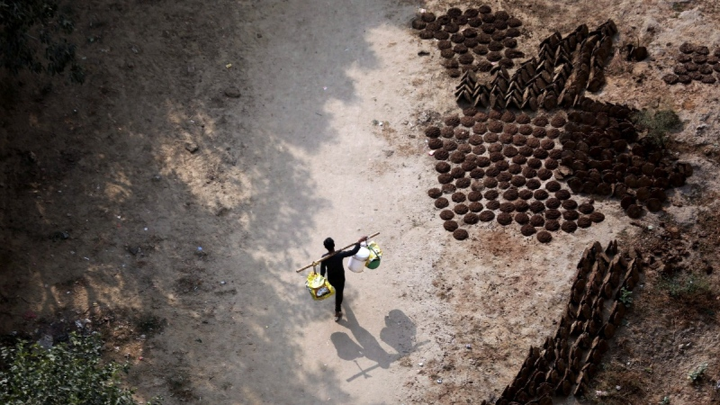 An Indian man carries plastic buckets as he walks past cow dung cakes used as a fuel for clay stoves, in New Delhi, India, on Dec. 8, 2018. (Altaf Qadri / AP)