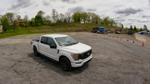 In this photo made on Thursday, May 6, 2021, a salesman from the Shults Ford dealership in Wexford, Pa. sits in one of the Ford F150 trucks at their nearby empty pickup truck inventory storage lot. Ford is warning that it expects to make only half the normal number of vehicles from now through June. Bazzy normally stocks 400-500 pickup trucks at his three Ford dealers, but is down around 100. He's confident that he can keep customers happy if they can order a truck and get it in four weeks, but he fears losing business to competing brands with a huge stock. (AP Photo/Keith Srakocic)