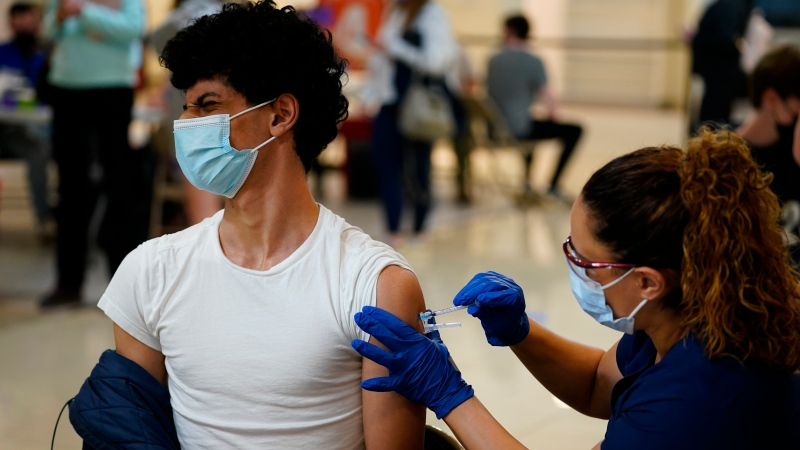 In this May 11, 2021, file photo, Nawaf Albarakati, 17, of Narberth, Pa., reacts as he receives a Pfizer COVID-19 vaccination from registered nurse Alicia Jimenez at a Montgomery County, Pa., Office of Public Health vaccination clinic at the King of Prussia Mall in King of Prussia., Pa. (AP Photo/Matt Slocum, File)
