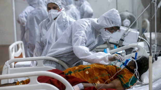 A health worker tries to adjust the oxygen mask of a patient at the BKC jumbo field hospital, one of the largest COVID-19 facilities in Mumbai, India, Thursday, May 6, 2021.(AP Photo/Rafiq Maqbool)