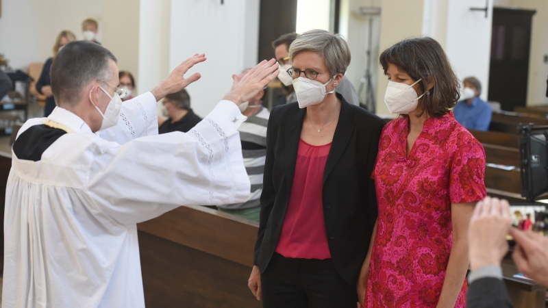 Vicar Wolfgang Rothe, left, blesses the couple Christine Walter, center, and Almut Muenster, right, during a Catholic service with the blessing of same-sex couples in St Benedict's Church in Munich, Sunday, May 9, 2021. (Felix Hoerhager/dpa via AP)