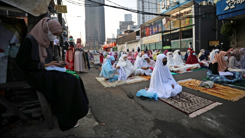 A Muslim woman checks her mobile phone as others sit spaced apart to help curb the spread of coronavirus outbreak prior to the start of an Eid al-Fitr prayer marking the end of the holy fasting month of Ramadan on a street in Jakarta, Indonesia, Thursday, May 13, 2021. (AP Photo/Dita Alangkara)