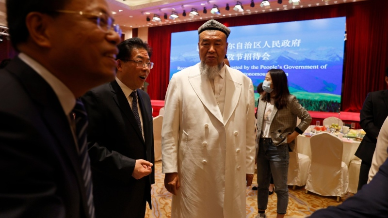 Abdureqip Tomurniyaz, who heads the association and the school for Islamic studies in Xinjiang, looks over at other Chinese government officials during a reception held for the Eid al-Fitr festival in Beijing on May 13, 2021. (Ng Han Guan / AP)
