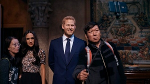 A couple takes a selfie with wax sculptures of Meghan Markle, second left, and Prince Harry, second right, during an event at the Madame Tussauds wax museum in New York, on May 19, 2018. (Andres Kudacki / AP)