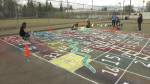 A gigantic Snakes and Ladders was painted at the Parkview Community League on May 12, 2021, by area resident Kristie Edwardsen and a handful of volunteers.