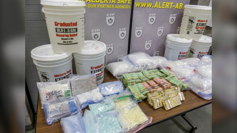 Some of the drugs and cash seized by ALERT, including 113.5 litres of GHB, which police say this is the largest ever seizure in Alberta. (ALERT handout)