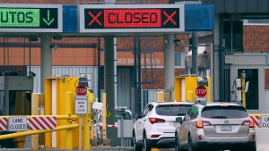 """Vehicles wait in line to cross into Canada at the Peace Bridge Plaza, Wednesday, March 18, 2020, in Buffalo N.Y. The Canada-U.S. border will be closed to non-essential traffic in both directions """"by mutual consent,"""" President Donald Trump confirmed Wednesday, as efforts across the continent to contain the widening COVID-19 pandemic continued to upend daily life in North America. (AP Photo/Jeffrey T. Barnes)"""