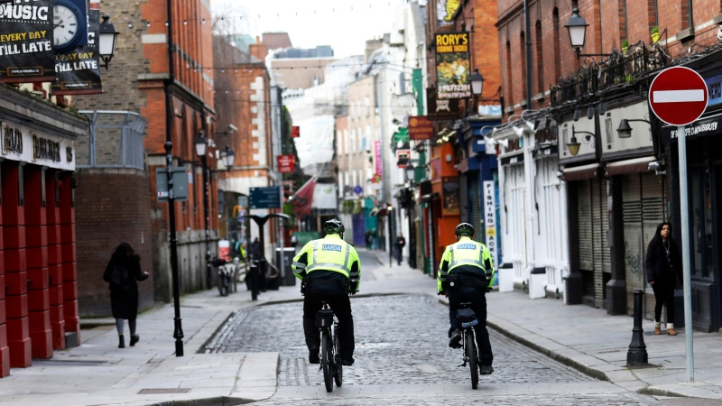 Garda police officers patrol a deserted Temple Bar in Dublin, Ireland, Wednesday, March, 17, 2021. (AP Photo/Peter Morrison)