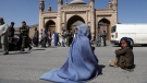 FILE - An Afghan woman waits for alms during the first day of Eid al-Fitr in Kabul, Afghanistan, Thursday, May 13, 2021. Eid al-Fitr prayer marks the end of the holy fasting month of Ramadan in Afghanistan. (AP Photo/Rahmat Gul)