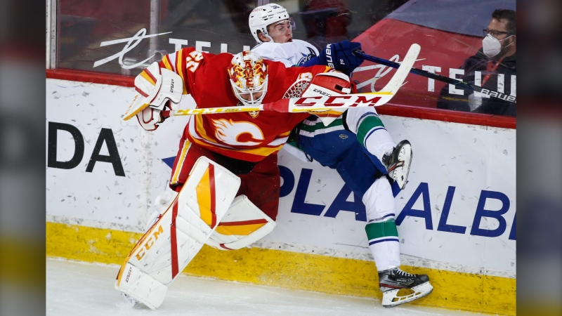 Vancouver Canucks' Nils Hoglander, right, is checked by Calgary Flames goalie Jacob Markstrom during third period NHL hockey action in Calgary, Thursday, May 13, 2021.(THE CANADIAN PRESS/Jeff McIntosh)
