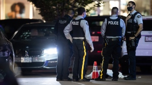 RCMP officers stand near a body covered with a tarp in the parking lot of a shopping complex after one person was killed and two others were injured during a shooting in Burnaby, B.C., on Thursday, May 13, 2021. THE CANADIAN PRESS/Darryl Dyck