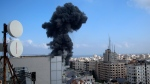 Smoke rises following Israeli airstrikes on a buildingin Gaza City, Thursday, May 13, 2021. Israeli airstrikes killed multiple senior Hamas military figures Wednesday and toppled a pair of high-rise towers housing Hamas facilities. (AP Photo/Hatem Moussa)