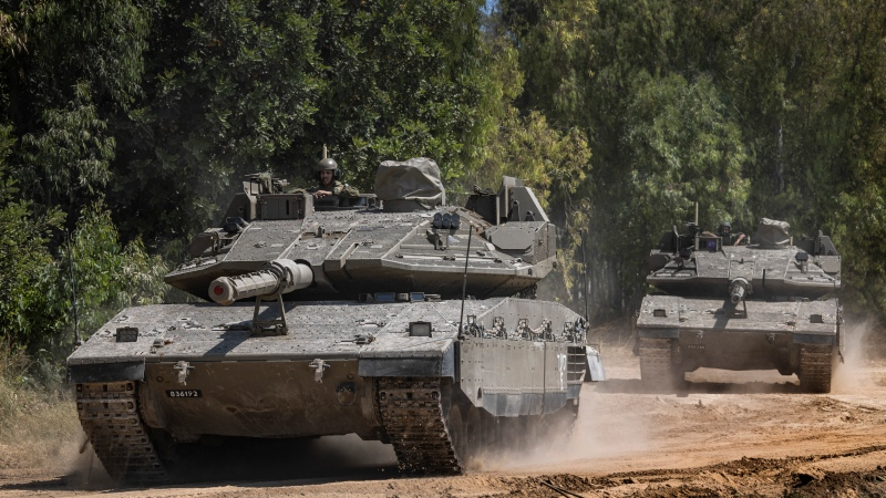 Israeli tanks cross a road as they advances towards a staging ground near the Israeli Gaza border, May 14, 2021. (AP Photo/Tsafrir Abayov)