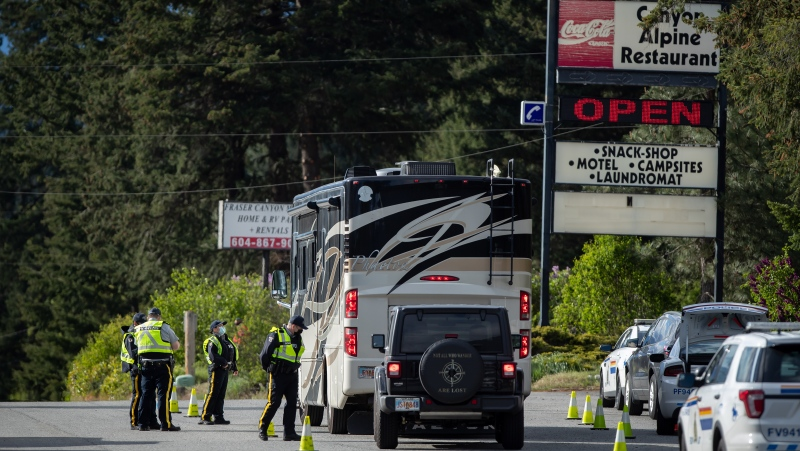 An RCMP officer speaks with a motorist in a recreational vehicle traveling to Alaska, at a COVID-19 travel checkpoint on the Trans-Canada Highway north of Boston Bar, B.C., on Friday, May 7, 2021. Due to COVID-19 non-essential travel is banned between the province's three designated travel regions: the Lower Mainland and Fraser Valley; Vancouver Island; and the Northern and Interior areas. Current restrictions are in place until at least May 25. THE CANADIAN PRESS/Darryl Dyck