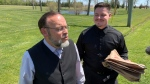 Church of God Pastor Henry Hildebrandt, left, and Assistant Pastor Peter Wall speak outside the church in Aylmer, Ont. after a judge ordered the doors locked on Friday, May 14, 2021. (Bryan Bicknell / CTV News)