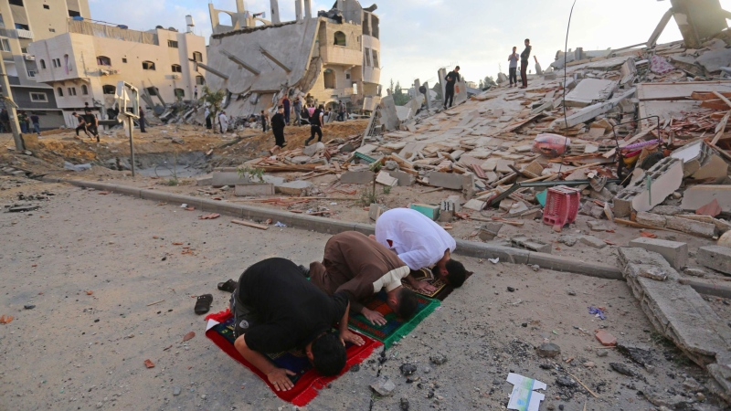 Palestinians perform Eid al-Fitr prayers near buildings destroyed by ongoing Israeli airstrikes in Beit Lahia, Gaza, on May 13. (Ashraf Amra/Anadolu Agency/Getty Images via CNN)