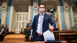 Quebec Justice Minister Simon Jolin-Barrette, responsible for French language, hold a copy of a legislation to modify the language law before presenting it, Thursday, May 13, 2021 at the legislature in Quebec City. THE CANADIAN PRESS/Jacques Boissinot