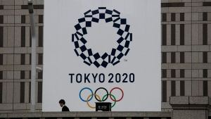 A man walks past a large banner promoting the Tokyo 2020 Olympics in Tokyo, Monday, March 23, 2020.  (AP Photo/Jae C. Hong)
