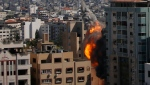 An Israeli airstrike hits the high-rise building housing The Associated Press' offices in Gaza City, Saturday, May 15, 2021. The airstrike Saturday came roughly an hour after the Israeli military ordered people to evacuate the building. There was no immediate explanation for why the building was targeted. The building housed The Associated Press, Al-Jazeera and a number of offices and apartment. (AP Photo/Hatem Moussa)