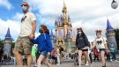 FILE - IN this Dec. 21, 2020 file photo, A family walks past Cinderella Castle in the Magic Kingdom, at Walt Disney World in Lake Buena Vista, Fla. (Joe Burbank/Orlando Sentinel via AP, File)