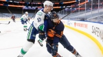 Edmonton Oilers' Jujhar Khaira (16) and Vancouver Canucks' Tyler Myers (57) battle for the puck during second period NHL action in Edmonton on Saturday, May 15, 2021 (The Canadian Press/Jason Franson)