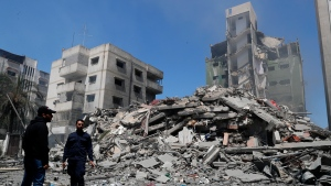 Hamas police officer stands guard amid the rubble of the Yazegi residential building that was destroyed by an Israeli airstrike, in Gaza City, Sunday, May 16, 2021. The 57-member Organization of Islamic Cooperation held an emergency virtual meeting Sunday over the situation in Gaza calling for an end to Israel's military attacks on the Gaza Strip. (AP Photo/Adel Hana)