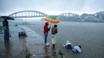 "Relatives of a person who died of reasons other than COVID-19 perform rituals in Periyar river during heavy rains in Kochi, Kerala state, India, Saturday, May 15, 2021. With cyclonic storm ""Tauktae"" intensifying over the Arabian Sea, the southern state is receiving heavy rains amid a lockdown imposed to curb the spread of coronavirus. (AP Photo/R S Iyer)"