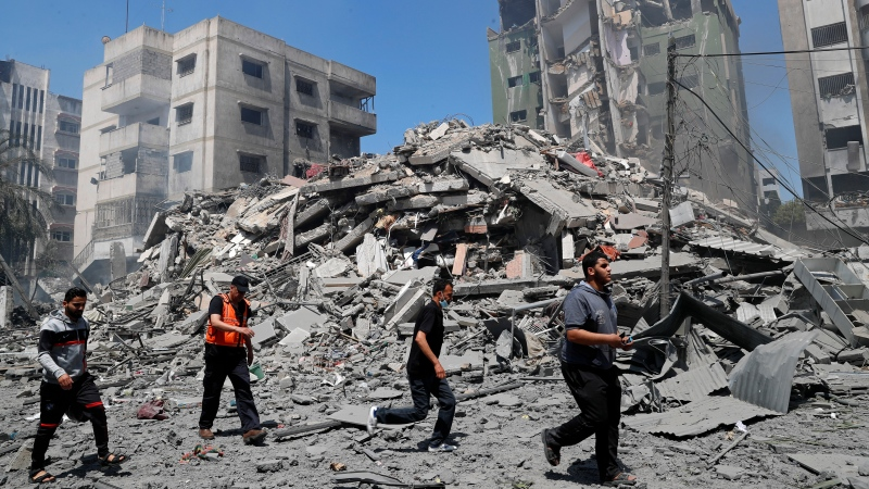 People inspect the the rubble of the Yazegi residential building that was destroyed by an Israeli airstrike, in Gaza City, Sunday, May 16, 2021. (AP Photo/Adel Hana)