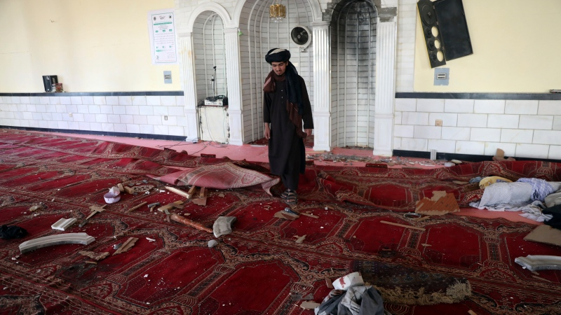 A religious student inspects inside a mosque after a bomb explosion in Shakar Dara district of Kabul, Afghanistan, Friday, May 14, 2021. A bomb ripped through a mosque in northern Kabul during Friday prayers killing 12 worshippers, Afghan police said. (AP Photo/Rahmat Gul)
