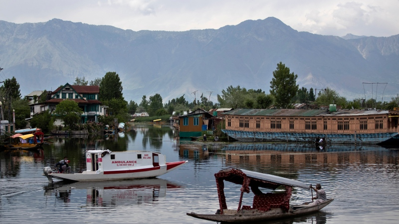A Kashmiri man on a water ambulance, left, uses a loud speaker asking people to stay indoors in Dal Lake during a lockdown imposed to curb the spread of coronavirus in Srinagar, Indian controlled Kashmir, Sunday, May 16, 2021. (AP Photo/Mukhtar Khan)