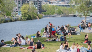 People gather next to the Lachine Canal on a warm spring day in Montreal, Saturday, May 15, 2021, as the COVID-19 pandemic continues in Canada and around the world. THE CANADIAN PRESS/Graham Hughes