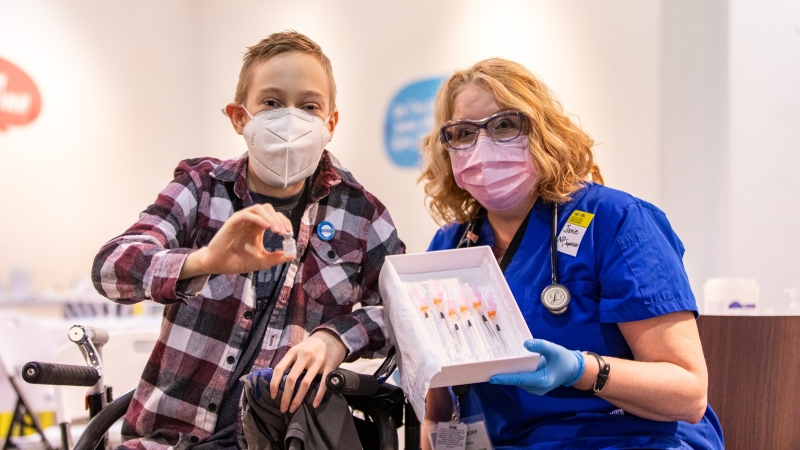 Riley Oldford, 16-years-old and who suffers from cerebral palsy, is the first N.W.T. youth to get the Pfizer vaccine poses for photos with Nurse practitioner Janie Neudorf in Yellowknife on Thursday May 6, 2021. THE CANADIAN PRESS/Bill Braden