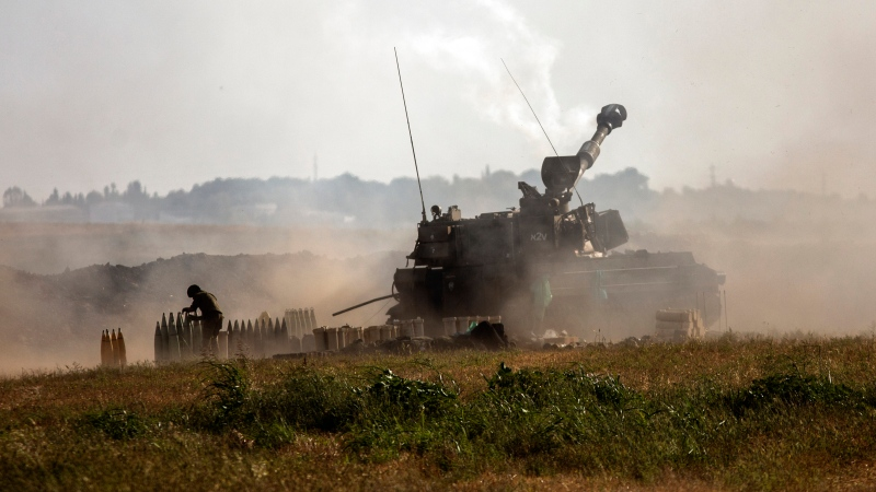 An Israeli artillery unit fires toward targets in the Gaza Strip, at the Israeli-Gaza border, Sunday, May 16, 2021. (AP Photo/Heidi Levine)
