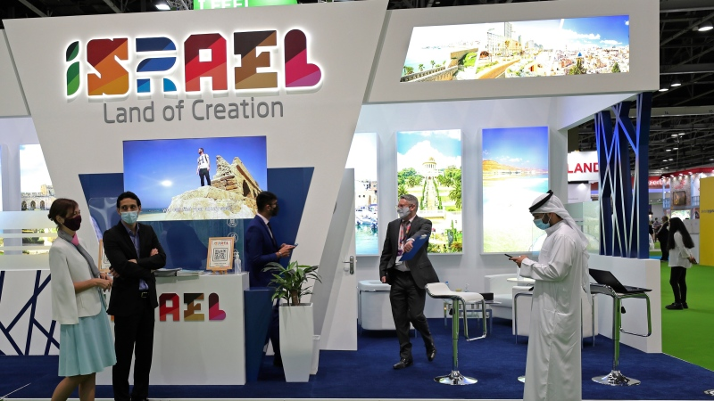 Israeli exhibitors receive visitors at their stand on the opening day of the Arabian Travel Market exhibition, in Dubai, United Arab Emirates, Sunday, May 16, 2021. As violence flares within Israel and on a day in which Israeli airstrikes on Gaza City killed at least 42 people Sunday, it was business as usual for a senior Israeli tourism official in Dubai as she promoted the country as a must-see destination for Muslim visitors. (AP Photo/Kamran Jebreili)